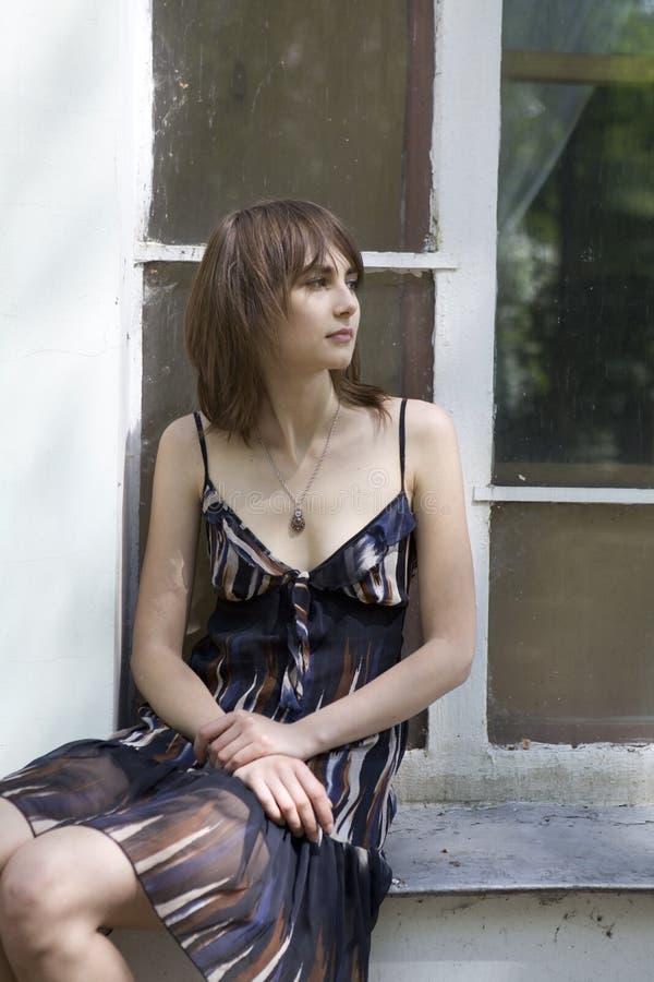 De peinzende zitting die van het tienermeisje op vensterbank FO wacht stock foto