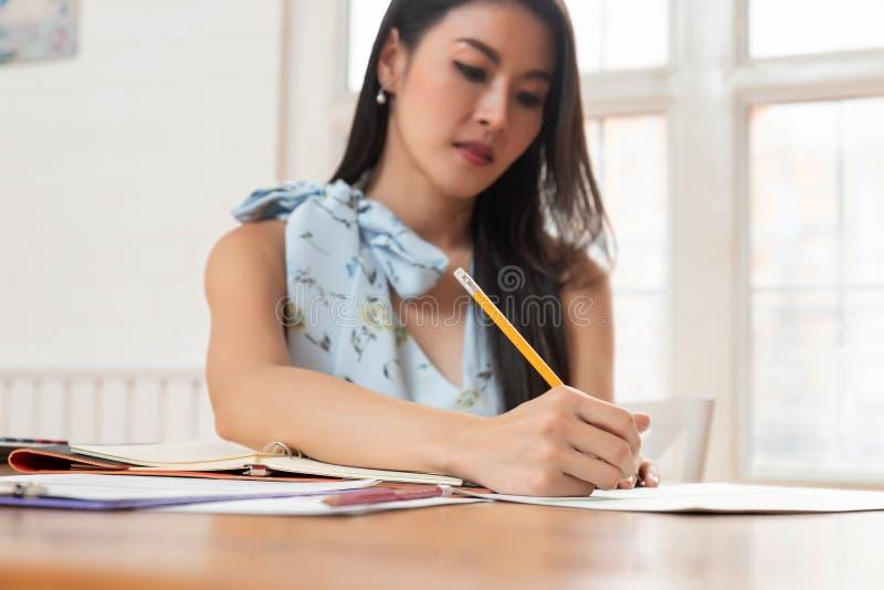 De pen Freelancer van de bedrijfsvrouwenholding terwijl het analyseren van bedrijfsgrafiek in koffie stock foto's