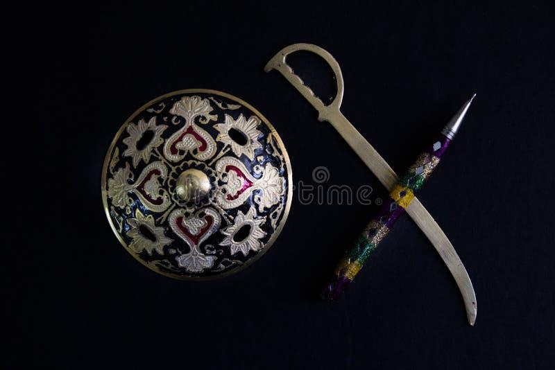 De pen is machtiger dan zwaardconcept door verfraaid om zwaardschild en pen op zwarte achtergrond antiek artefact royalty-vrije stock foto's