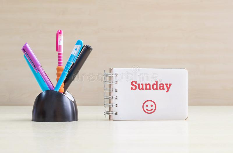 De pen van de close-upkleur met zwart ceramisch bureau proper voor pen en rood zondagwoord in witte pagina en gelukkige gezichtse stock foto