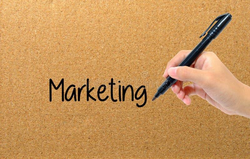 De pen van de handholding het schrijven woorden die zaken op de markt brengen stock afbeelding