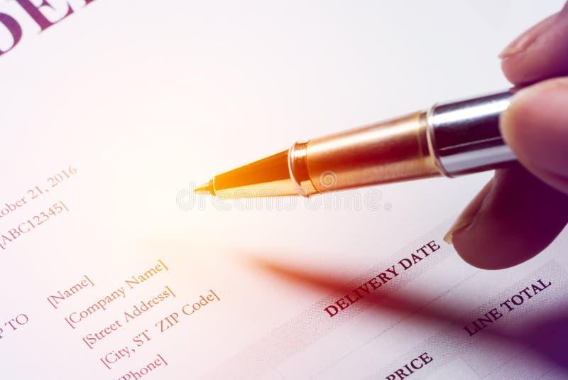 De pen van de handholding om tekst op kooporder te schrijven stock foto's