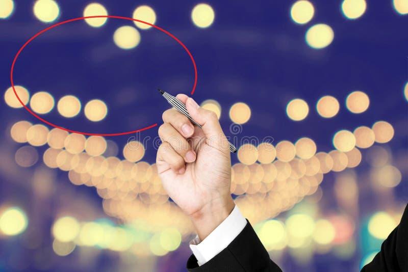 De pen van de zakenmanholding het schrijven cirkel, met de achtergrond van defocusbokeh stock fotografie