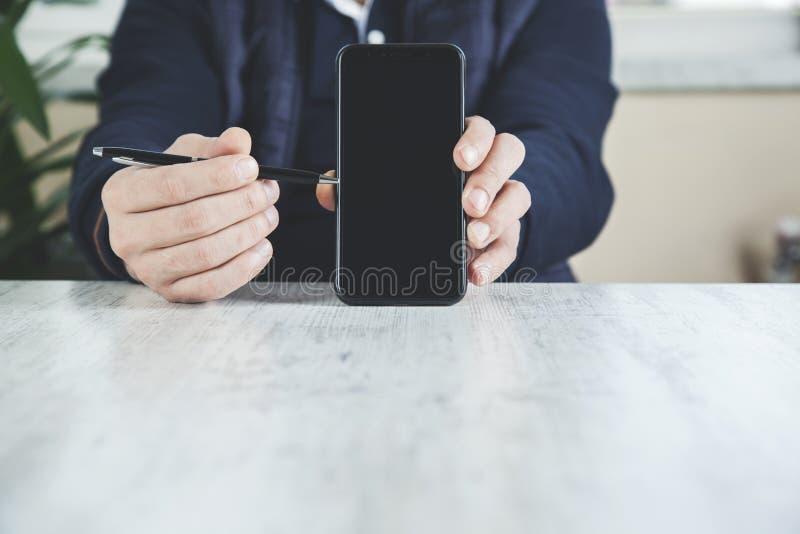 De pen van de mensenhand met telefoon stock afbeelding