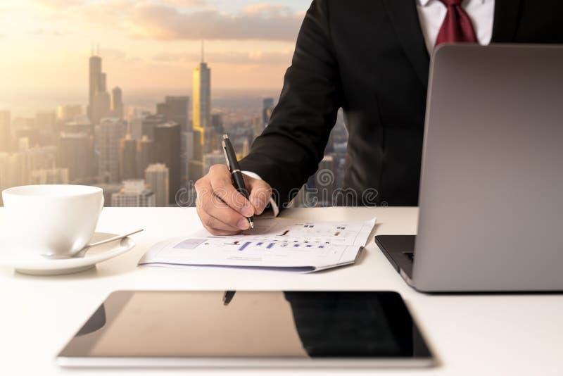 De pen van de de zakenmanholding van de hand en de analysegegevens brengen op document document en het bekijken computer moderne  royalty-vrije stock foto's