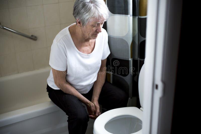 De pensioneringsvrouw viel neer in een toilet stock afbeeldingen