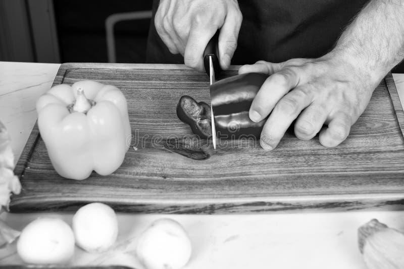De peper van de handplak met ceramisch mes Groenten worden die die op houten scherpe raad worden gesneden Voedsel voorbereiding e stock afbeeldingen