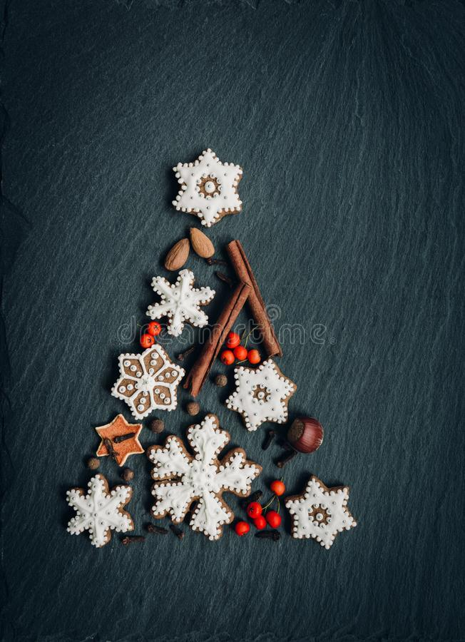 De peperkoek, noten, kruiden, droge sinaasappelschil leidt tot een Kerstboom op een donkere steenachtergrond royalty-vrije stock afbeelding
