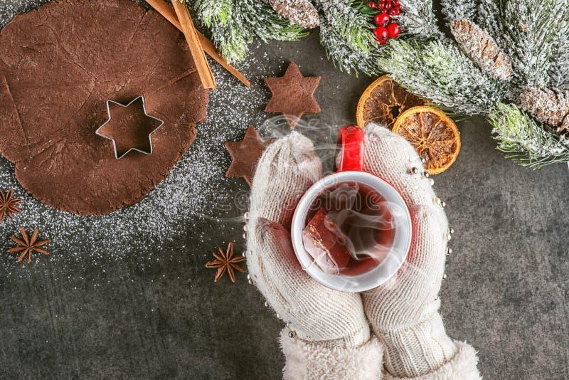 De peperkoek van het Kerstmisbaksel met kopod hierboven thee in handen en ingrediënten, traditionele Kerstmisachtergrond van royalty-vrije stock foto's