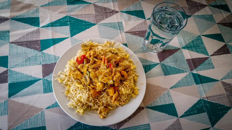 De pepersaus van de kippenpaddestoel met ongepelde rijst met glas van wate royalty-vrije stock foto's