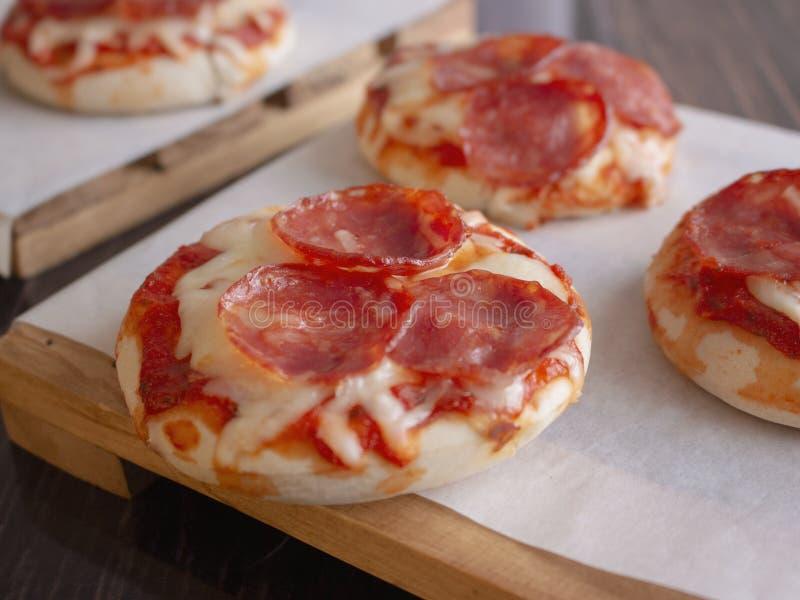 De pepperonis en de Mozarellakaas Mini Pizzas dienden op Houten Platen over Wit Voedseldocument royalty-vrije stock foto