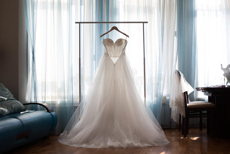 De perfecte huwelijkskleding met een volledige rok op een hanger stock afbeelding