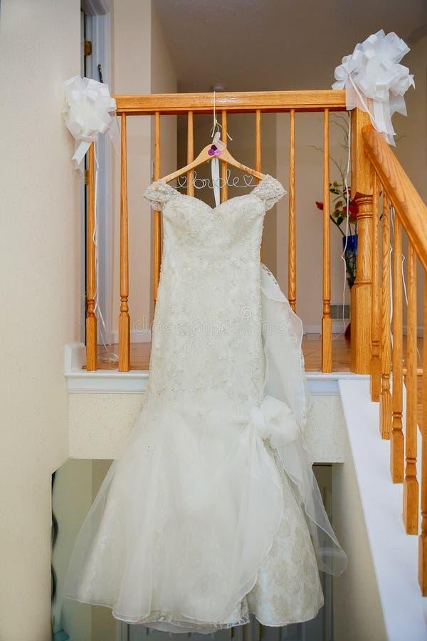 De perfecte huwelijkskleding met een volledige rok op een hanger in de ruimte stock afbeelding