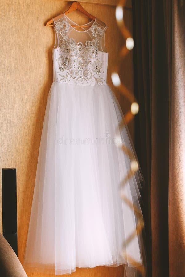 De perfecte huwelijkskleding met een volledige rok op een hanger in de ruimte van de bruid stock afbeelding