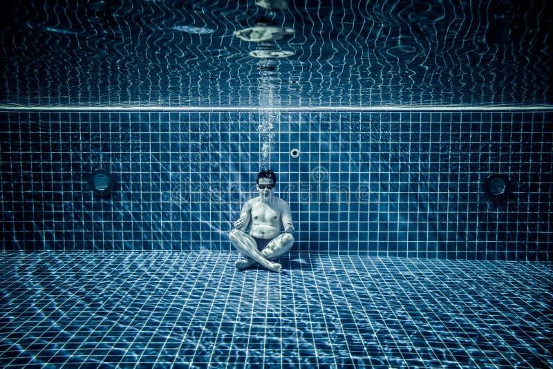 De personen ligt onder water in een zwembad stock afbeelding