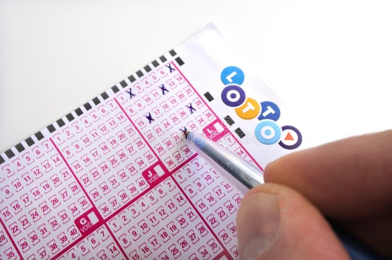 De persoon houdt een pen invullend aantallen op een loterijkaartje royalty-vrije stock afbeeldingen