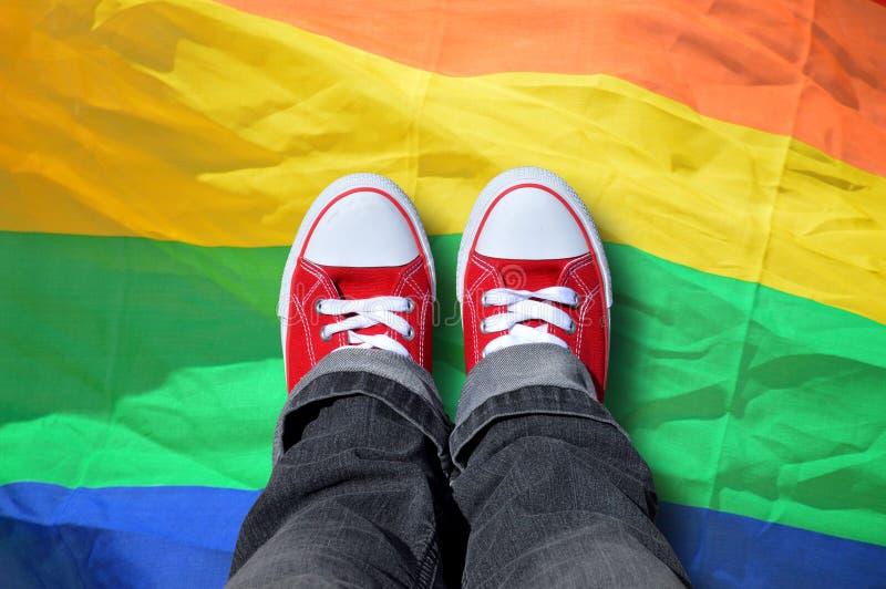 De persoon met tennisschoenen op regenboogvlag royalty-vrije stock afbeelding
