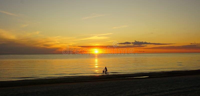 De persoon op de fiets bij het strand tijdens de zonsondergang royalty-vrije stock foto's