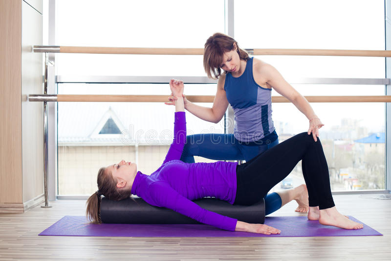 De persoonlijke trainer die van aerobicspilates vrouwen helpen royalty-vrije stock foto's