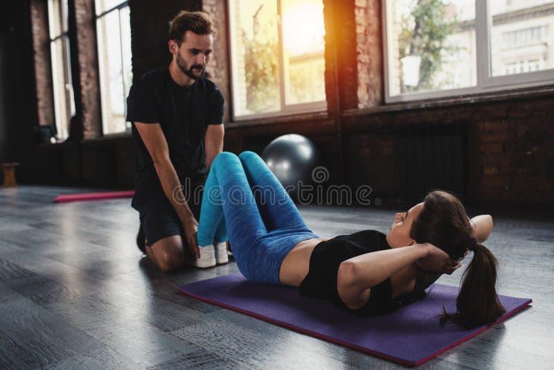 De persoonlijke trainer helpt een meisje met de gymnastiekoefeningen stock afbeeldingen