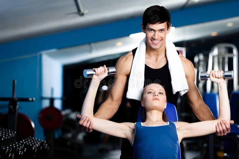 De persoonlijke trainer helpt vrouw om met gewichten uit te oefenen stock afbeelding