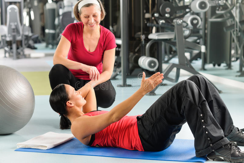 De persoonlijke trainer toont buikoefening op mat royalty-vrije stock foto