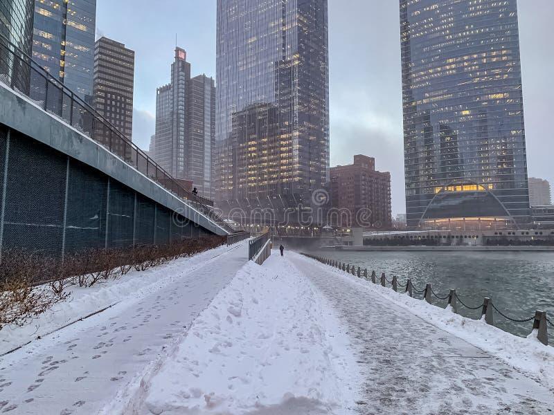 De persoonsgangen alleen op snow-covered riverwalk naast een vochtige Rivier van Chicago als temps werpen zich stock afbeelding