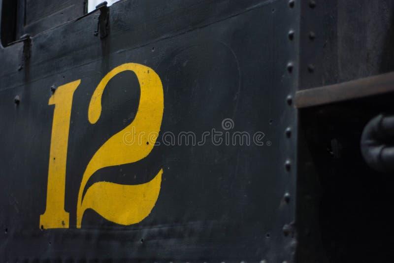 De perto do número amarelo doze em um carro de estrada de ferro preto imagens de stock royalty free