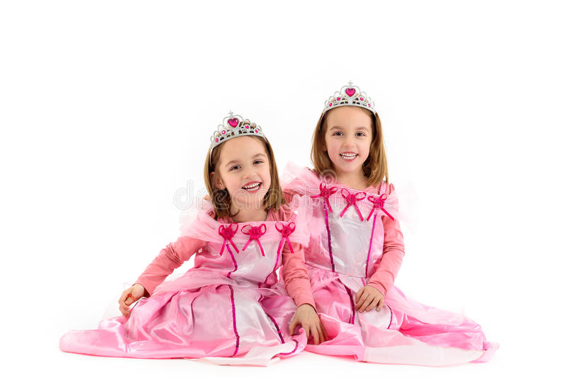De petites filles jumelles sont habillées comme princesse dans le rose photo stock