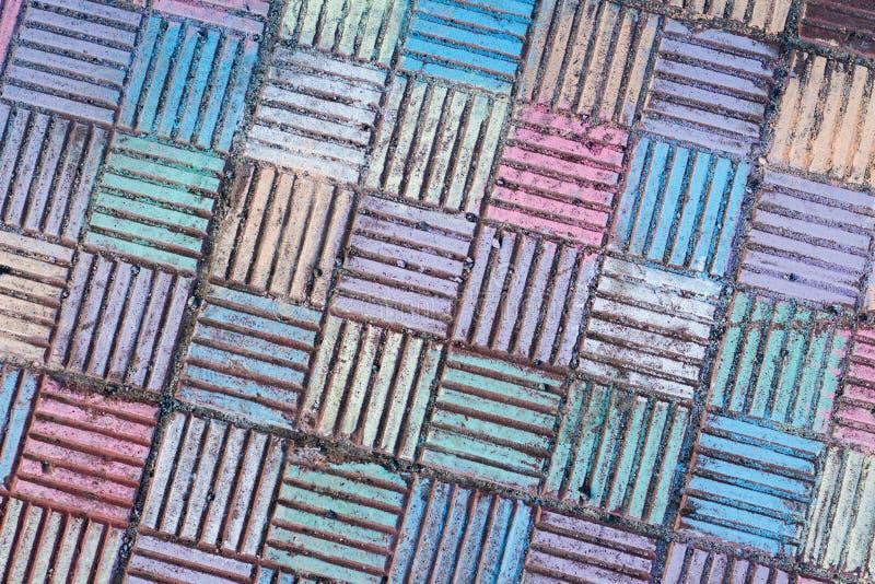 De petites formes concrètes sous forme de places sont peintes avec la craie de couleurs lumineuses et des nuances photo stock