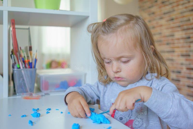 De peuter die van het babymeisje en met plasticine, close-upschot spelen leren stock fotografie