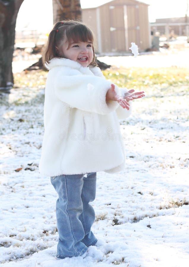De Peuter die van het meisje Sneeuw werpt royalty-vrije stock foto