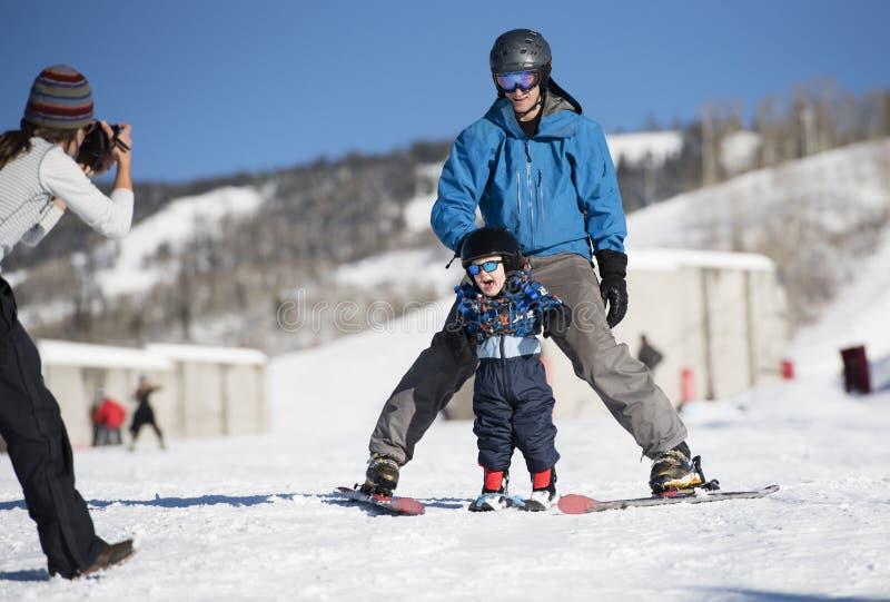 De peuter gilt met Verrukking aangezien hij om met Papa leert te skien terwijl het Mamma een Foto neemt stock afbeeldingen