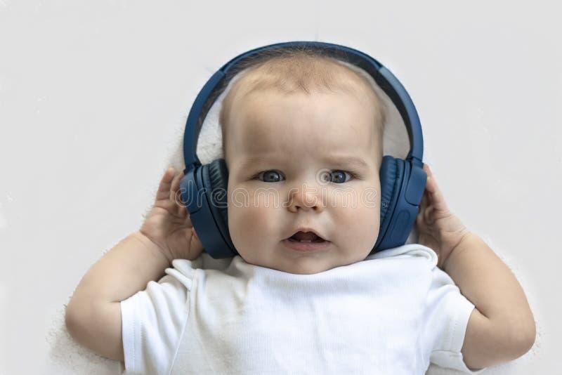 De Peuter van het babykind het Gelukkige glimlachen in draadloze blauwe hoofdtelefoons op een witte achtergrond Het concept techn stock fotografie