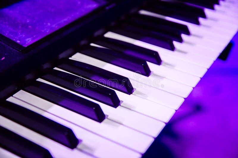 De piano sluit dicht omhoog in purper overleglicht stock foto's