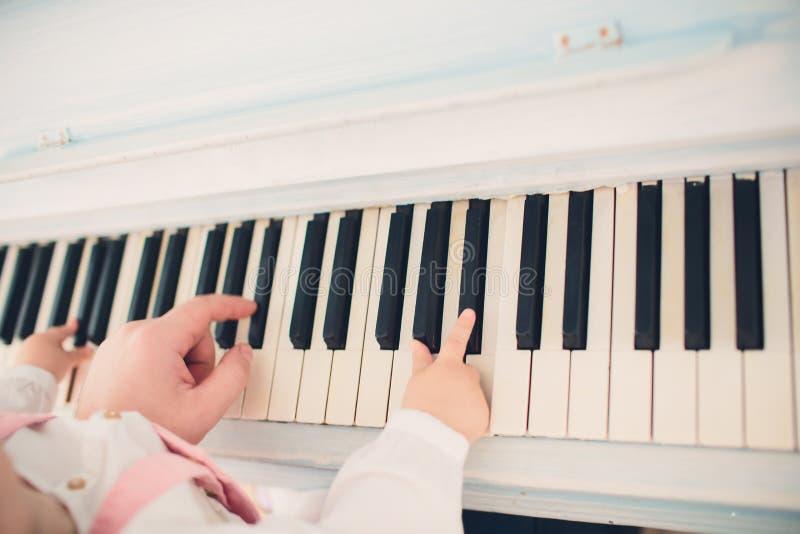 De pianoles van het vaderonderwijs aan het jonge geitje stock foto