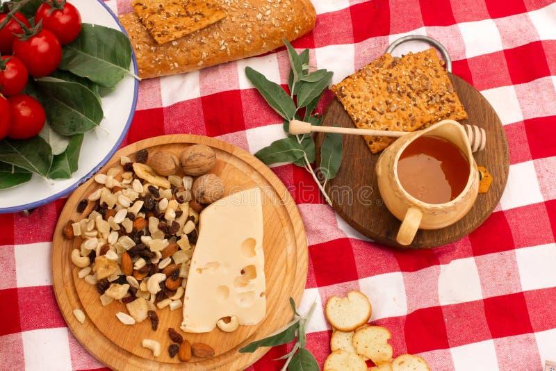 De picknick op de straat op een geruite deken spreidde uit voedsel uit Honing en noten op een houten dienblad, naast brood, kaas, royalty-vrije stock fotografie
