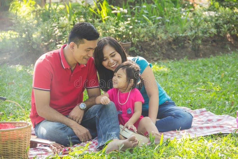 De picknick van de pretfamilie in een park stock fotografie