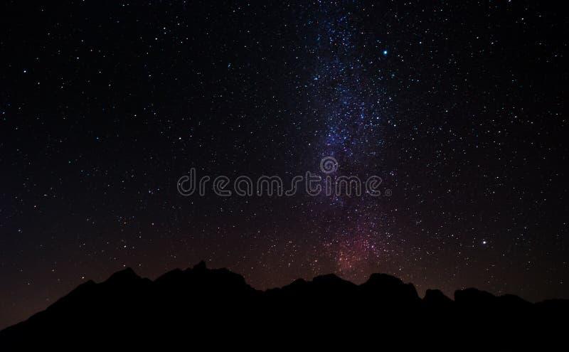 De piek van de silhouetberg bij nacht met hemelhoogtepunt van sterren en melkachtige manier stock afbeeldingen