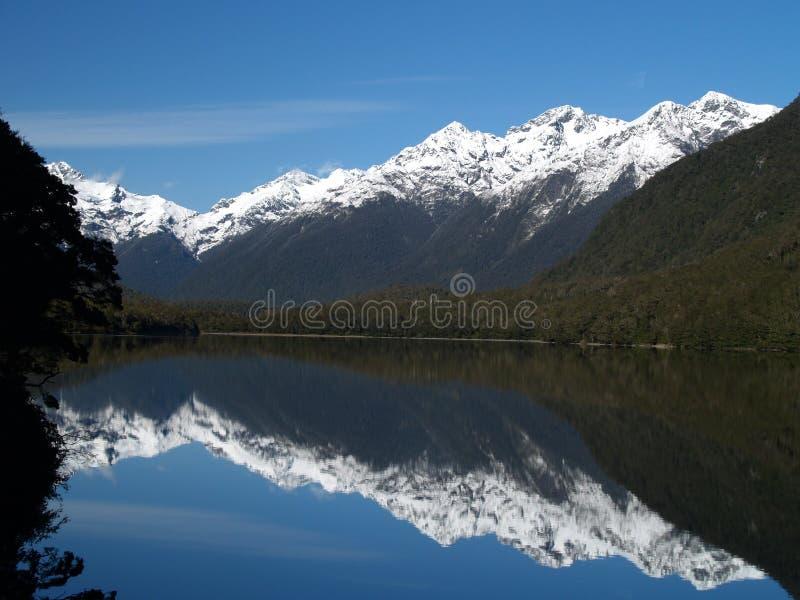 De piek van de sneeuw over spiegelmeer royalty-vrije stock foto