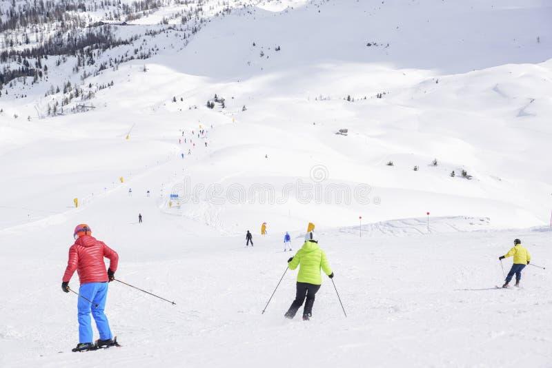 De pieken van de bergen van Alpen met sneeuw worden behandeld die de skihellingen overvol met skiërs op een zonnige de winterdag stock foto's