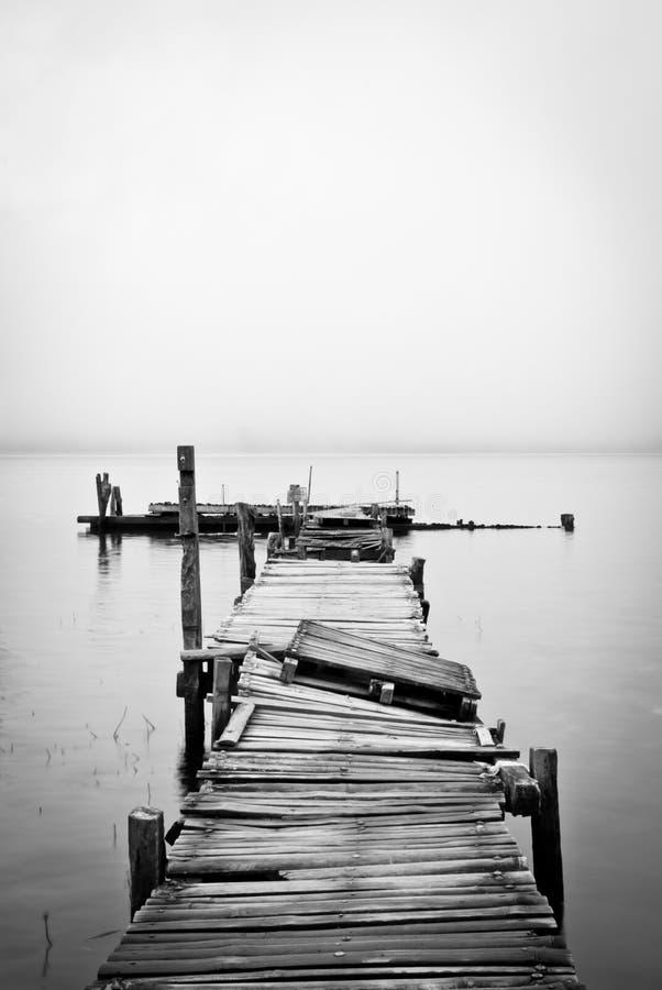 De pier van de oever van het meer onder een humeurige hemel royalty-vrije stock afbeeldingen