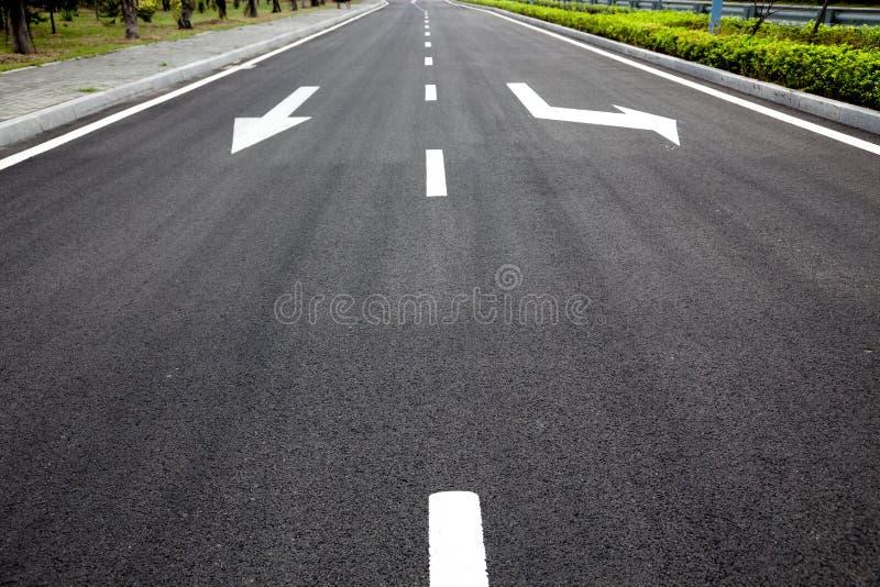 De pijlen van verkeersteken op geasfalteerde oppervlakte royalty-vrije stock foto's