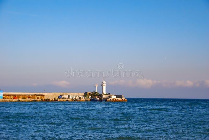 De pijler in het blauwe overzees, waardichtbij de boten zijn stock foto's