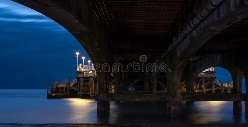 De Pijler van Bournemouth, UK, van onderaan onder de steunen, in laag licht in de ochtend vroeg wordt het gefotografeerd die stock foto