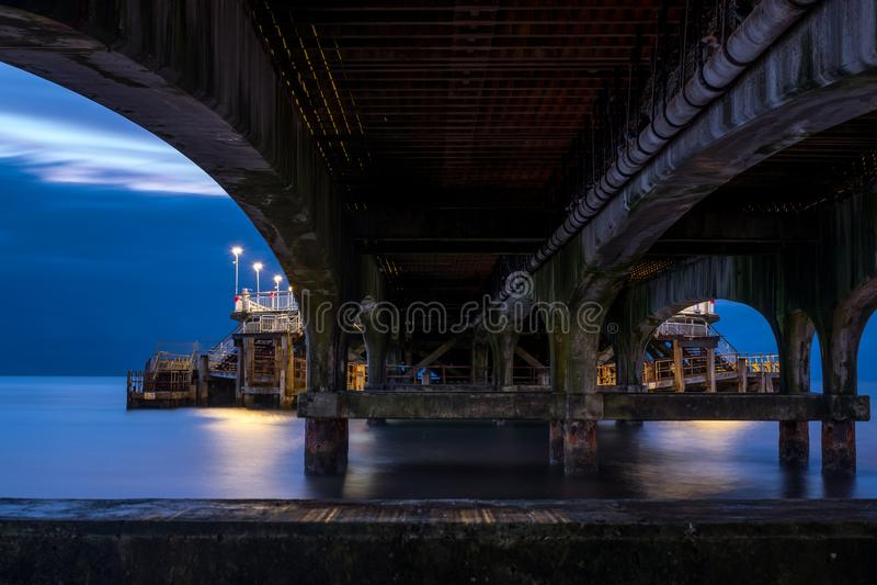De Pijler van Bournemouth, UK, van onderaan onder de steunen, in laag licht in de ochtend vroeg wordt het gefotografeerd die royalty-vrije stock fotografie