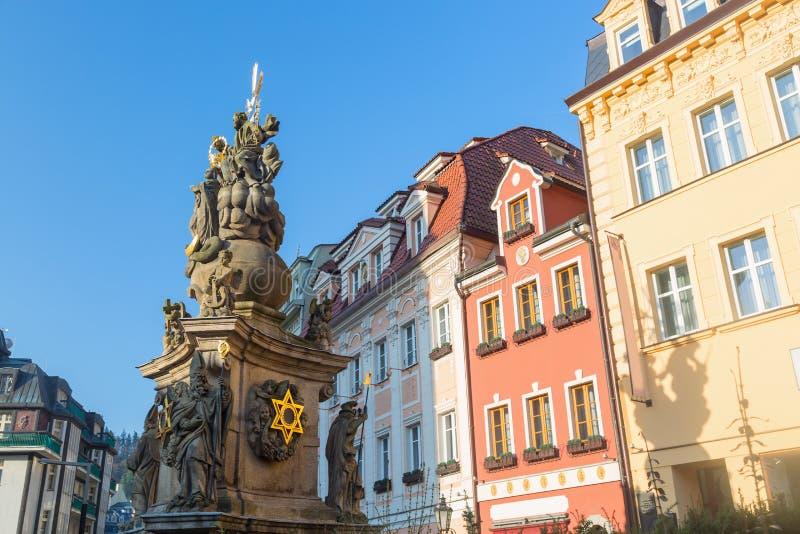 De pijler van de Heilige pijler van de Drievuldigheidsplaag met oude kleurrijke huizen tegen blauwe hemel in Karlovy varieert, Ts stock afbeelding