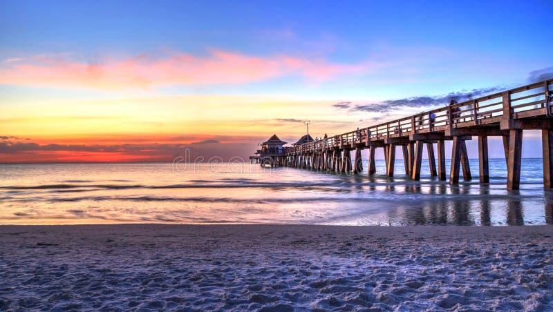 De Pijler van Napels op het strand bij zonsondergang stock afbeelding