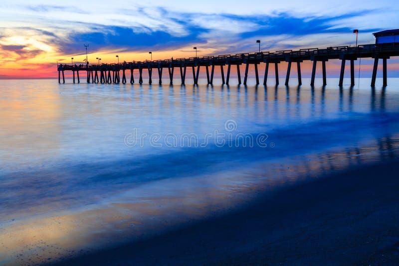 De pijler van Venetië, Florida, bij zonsondergang met opzettelijk onscherpe golven om moties en schoonheid te tonen stock foto's