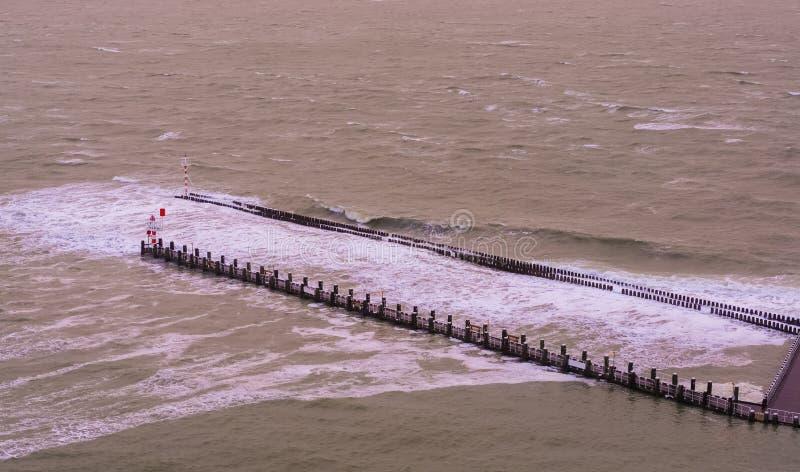 De pijlerpier van vlissingen met houten polen en kleine vuurtoren, wilde overzees met golven bij hoogtijd, Zeeland, Nederland stock foto's